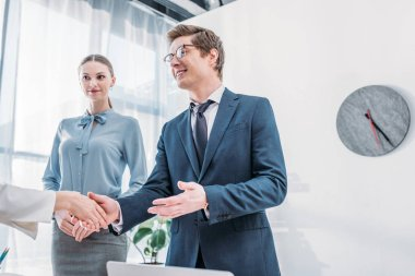 low angle view of cheerful recruiter shaking hands with woman near attractive colleague in office