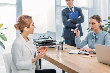 attractive woman talking with recruiter near coworker during job interview