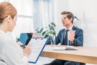 selective focus of recruiter writing on clipboard near man talking on job interview