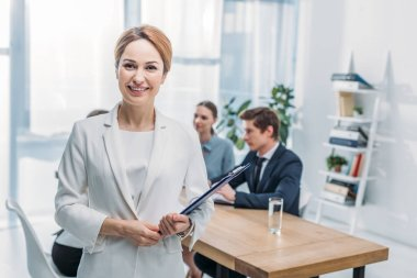 Selective focus of cheerful recruiter standing with clipboard near coworkers stock vector