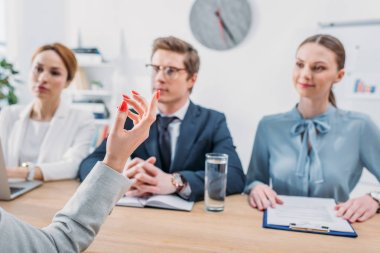 selective focus of female hand gesturing near recruiters during job interview