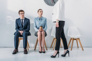 cropped view of recruiter standing near attractive woman and handsome man in glasses