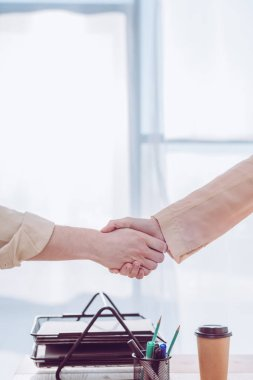 Cropped view of recruiter and employee shaking hands stock vector