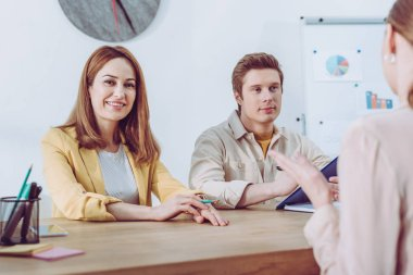 handsome recruiter sitting near cheerful colleague and looking at woman during job interview