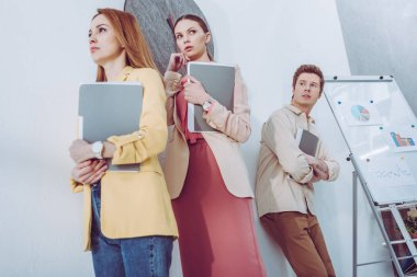 low angle view of worried attractive women and man waiting in line with folders