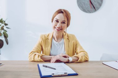 Happy recruiter in yellow jacket sitting near clipboard and pen stock vector