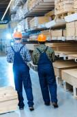 Fotografia vista posteriore di due lavoratori multiculturali in tuta e caschi in magazzino