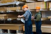 dva multikulturní pracovníci v uniformním postavení v blízkosti dřevěných stavebních materiálů