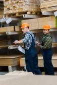 dva multikulturní dělníci se schránkymi stojící blízko dřevěných stavebních materiálů