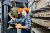 multicultural workers in uniform and plaid shirts working in warehouse
