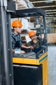 Fotografie handsome, attentive worker in helmet sitting in forklift machine near indian colleague talking on walkie talkie