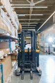 carrello elevatore in magazzino vicino a rack con materiali da costruzione in legno