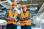 Ernsthafte multikulturelle Arbeiter in Schutzanzügen und Helmen blicken in die Kamera