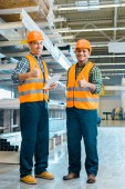 cheerful multicultural workers smiling and showing thumbs up