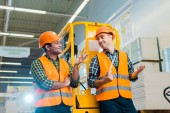 Fotografie cheerful multicultural workers talking and gesturing while standing near scissor lift