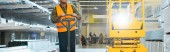 Photo panoramic shot of indian worker in safety vest near pallet jack in warehouse