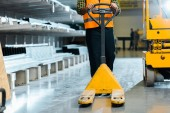partial view of warehouse worker standing with pallet jack near scissor lift