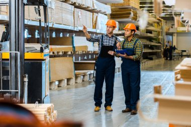 serious storehouse worker in uniform pointing with finger while standing near indian colleague