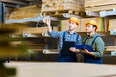 Selective focus of two multicultural storehouse workers with clipboards standing in warehouse stock vector