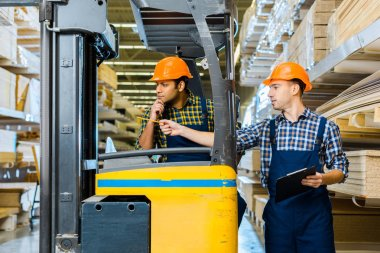indian warehouse worker sitting in forklift machine near colleague pointing with pencil