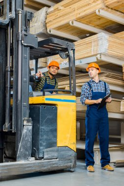 indian worker in forklift machine pointing with finger near colleague with clipboard