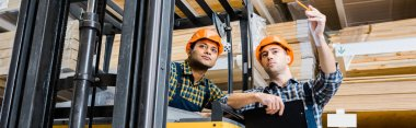 panoramic shot of warehouse worker pointing with pencil near indian colleague
