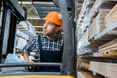 attentive warehouse worker in uniform and helmet operating forklift machine