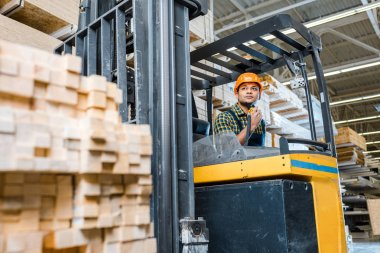 selective focus of indian warehouse worker sitting in forklift machine