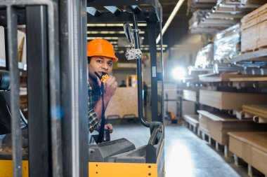 handsome indian worker sitting in forklift machine in warehouse and talking on walkie talkie