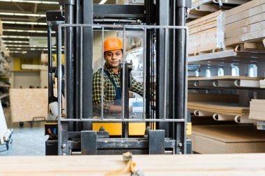 selective focus of handsome, conentrated indian worker sitting in forklift machine in warehouse