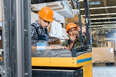 warehouse worker in helmet sitting in forklift machine near indian colleague talking on walkie talkie