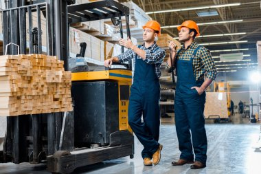 handsome multicultural warehouse workers in helmets standing near forklift machine in warehouse