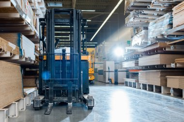 forklift machine in warehouse near shelves with wooden construction materials