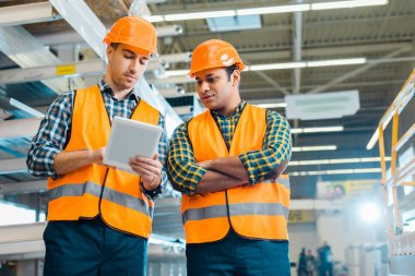 multicultural, concentrated workers using digital tablet in warehouse