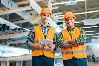 handsome multicultural workers in safety vasts and helmets smiling and looking at camera