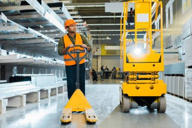 serious indian worker in safety vest and helmet standing near pallet jack in warehouse