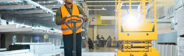 panoramic shot of indian worker in safety vest near pallet jack in warehouse