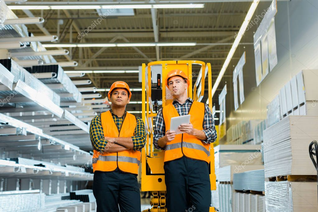 Selective focus of serious multicultural workers standing near scissor lift stock vector