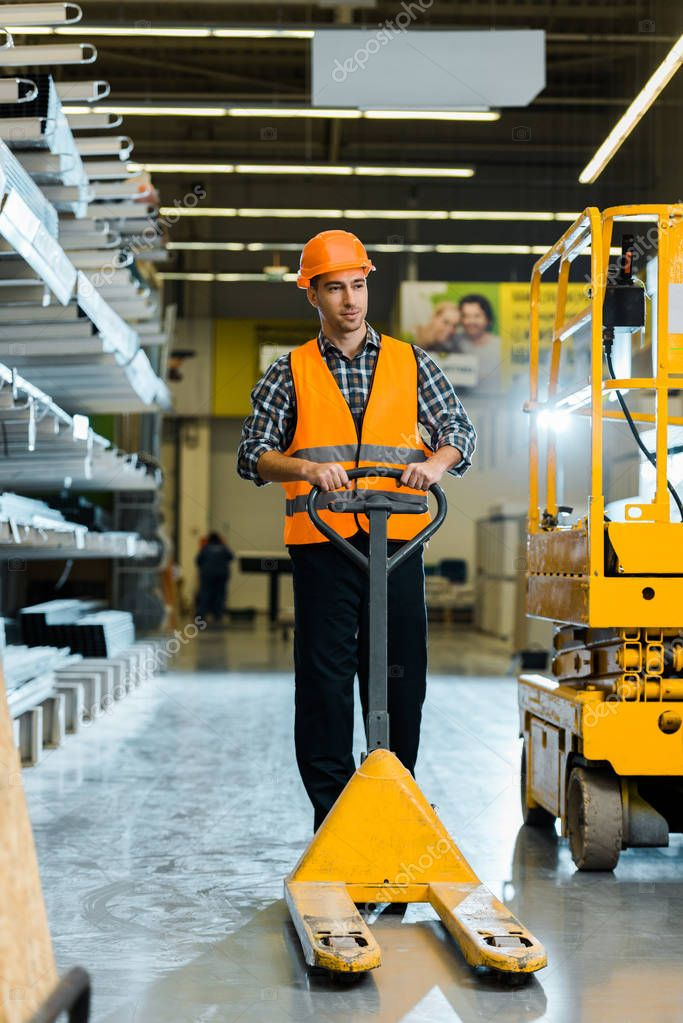 Handsome warehouse worker standing with pallet jack near scissor lift stock vector