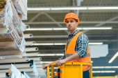 handsome, serious worker standing on scissor lift in warehouse
