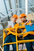 Fotografie serious multicultural warehouse workers using digital tablet while standing on scissor lift