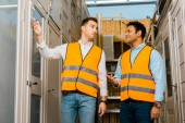 multicultural warehouse workers talking while standing in doors department