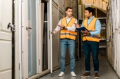 handsome multicultural storehouse workers talking while standing in doors department
