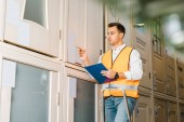 selective focus of worker in safety vest standing on ladder in warehouse