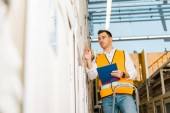selective focus of handsome, attentive worker standing on ladder and holding clipboard