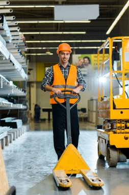 Cheerful warehouse worker standing with pallet jack, smiling and looking at camera stock vector