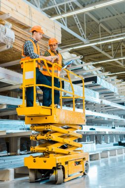 multicultural warehouse workers with digital tablet and clipboard standing on scissor lift
