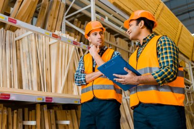 thoughtful multicultural workers standing near shelves with wooden construction materials