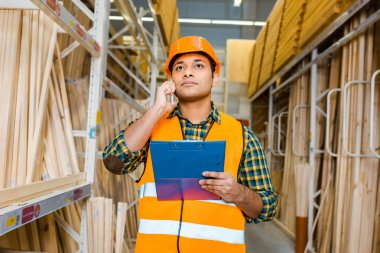 serious indian worker talking on smartphone and holding clipboard in warehouse