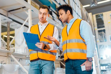 multicultural warehouse workers in safety vests working in plumbing department